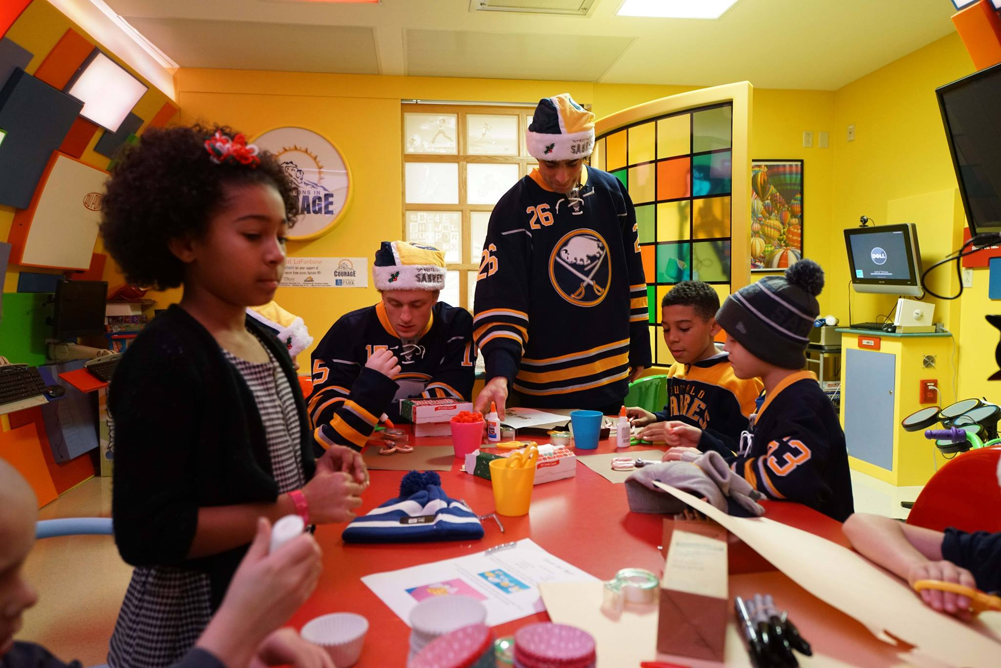 Jack Eichel and Matt Moulson work on crafts with young patients in the Lion's Den during a visit to RPCI on December 16, 2015.