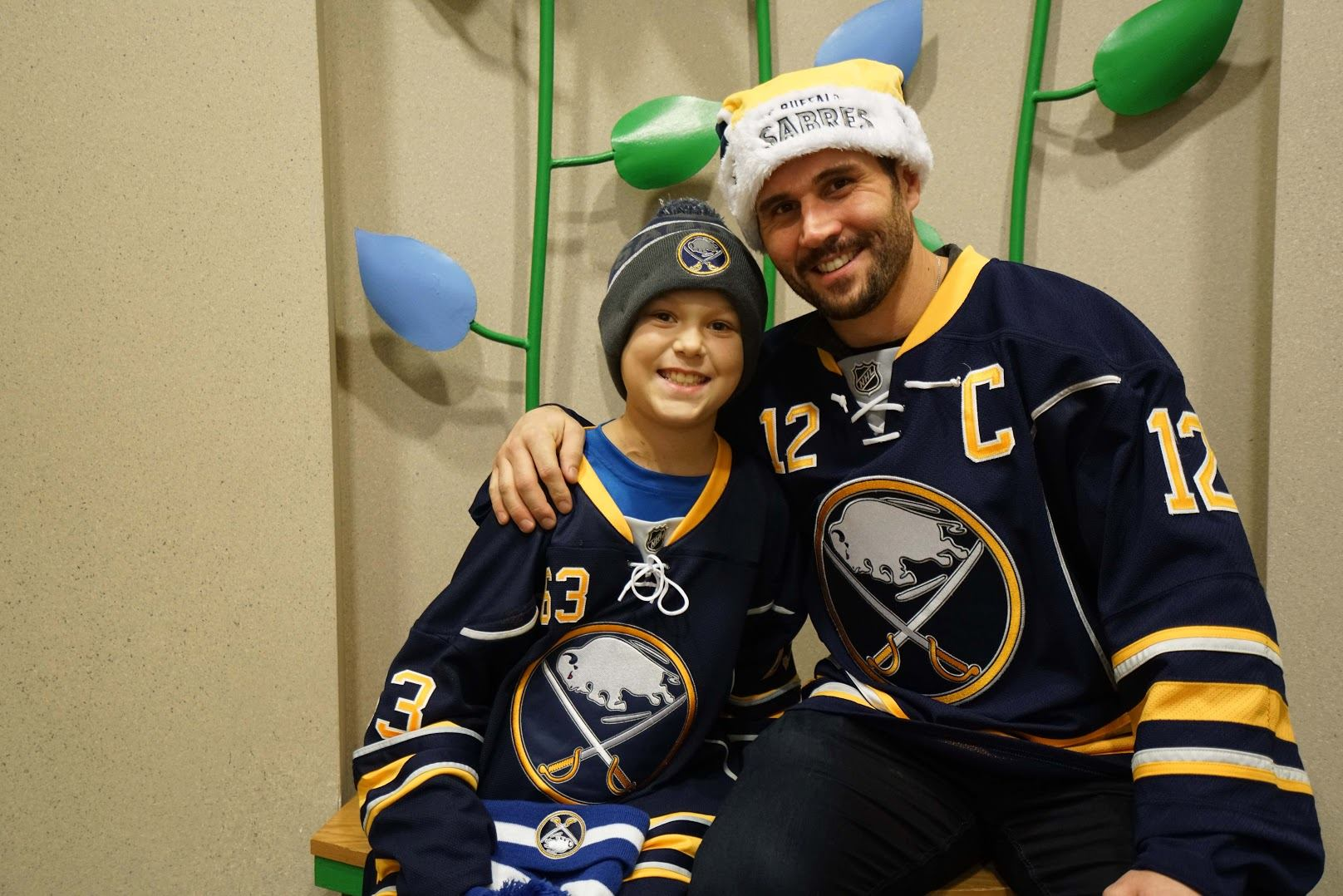 Sabres captain Brian Gionta meets with a young patient during a visit to RPCI on December 16, 2015.
