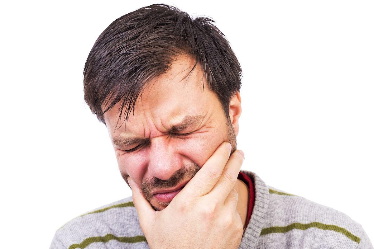 Man in pain holding his mouth