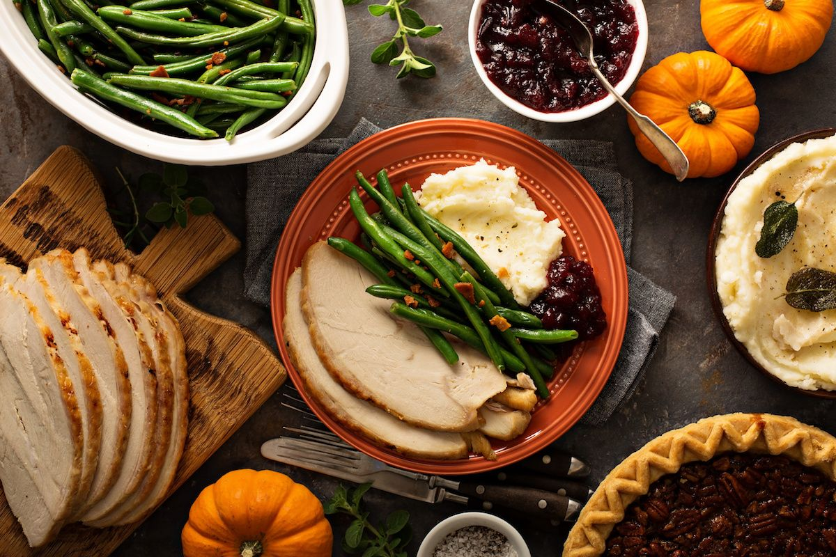 Holiday foods on a table, including turkey, green beans, mashed potatoes and pecan pie