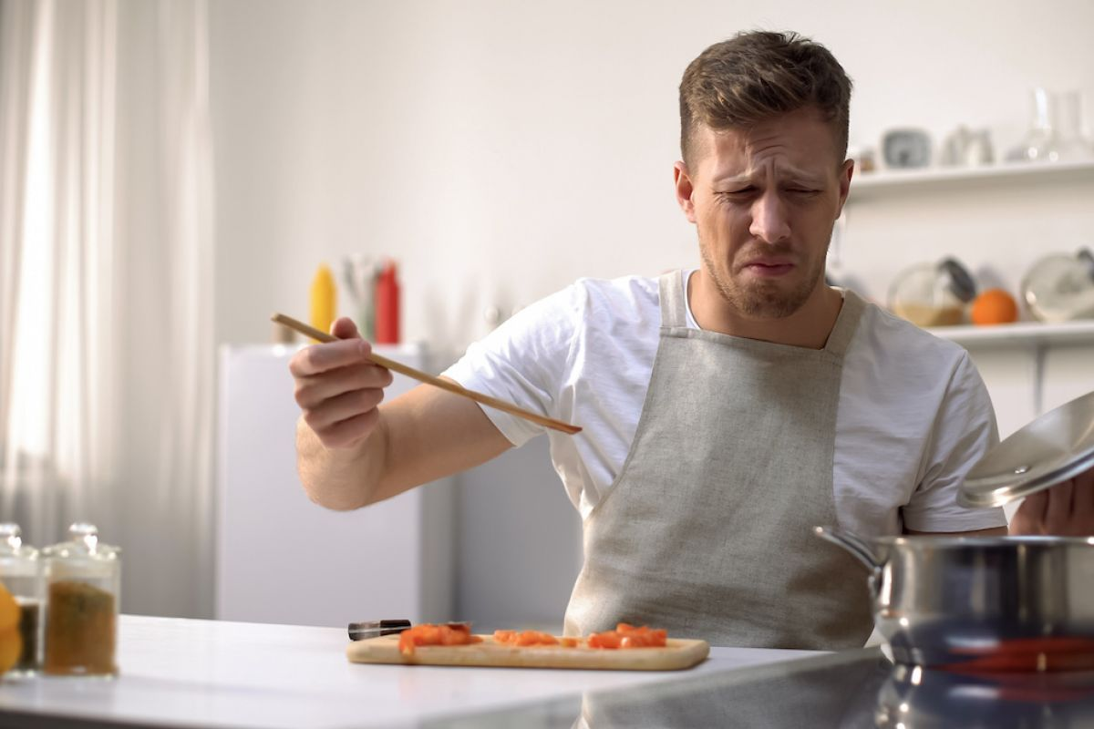 Man looks disgusted after tasting something he is cooking