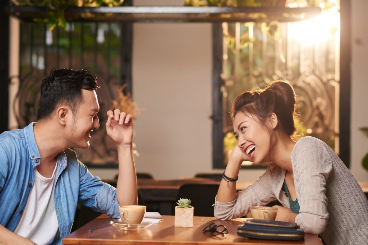 Couple on a date sitting at a table and laughing.