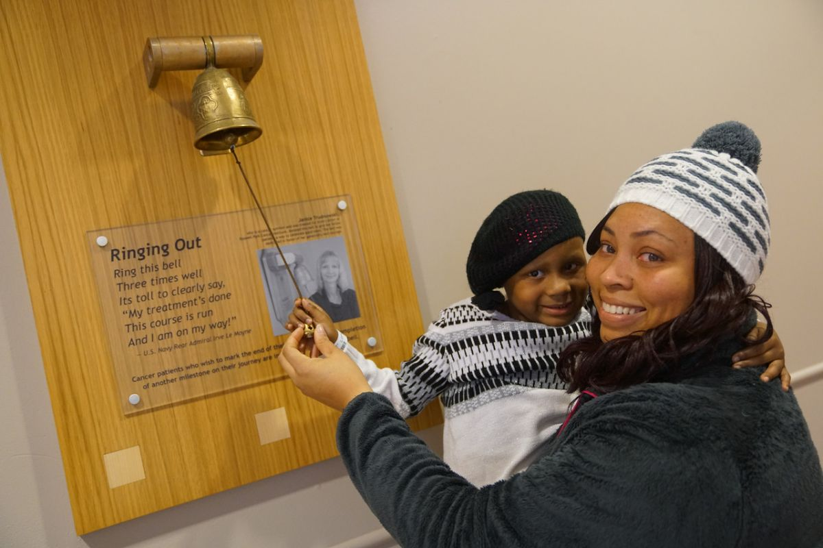 Ariel Riddick, a single mother, helps her daughter Natalie Morley ring the Roswell Park Victory Bell.
