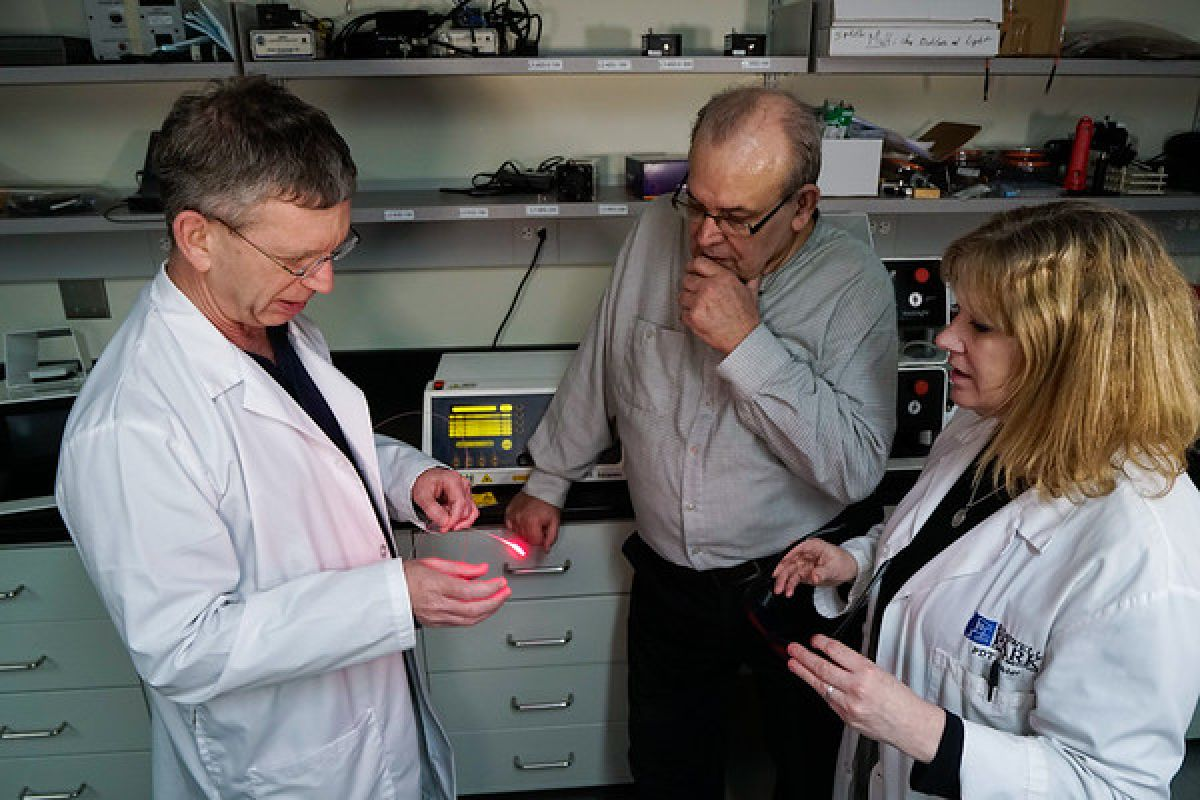Gal Shafirstein, DSc, Director of PDT Clinical Research (left), and PDT Nurse Michele Cooper, RN, BSN (right), show George Grace the type of laser that was used for his treatment with photodynamic therapy.
