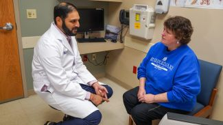 Dr. Ajay Abad consults with a patient before receiving Chemotherapy.