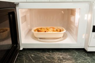 Microwave containing food in a plastic container