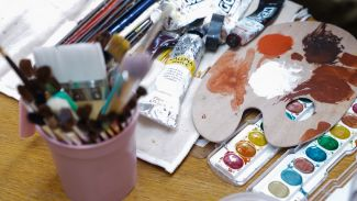 Watercolors, paint tubes, brushes, and other art supplies