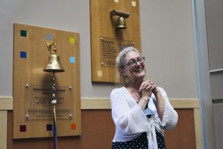 Lady is joyful as she is about to ring the bell at Roswell Park