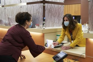 A Roswell Park pharmacist hands a prescription to a patient.