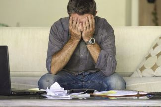 Stock image - worried man with paperwork