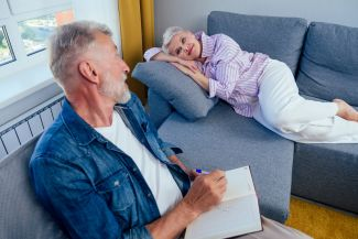 Man writing in book as woman lies on sofa