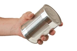 Hand holding a metal food can